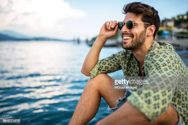 handsome smiling man looking away. - standing water stock pictures, royalty-free photos & images