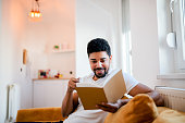 Handsome smiling man reading a book while sitting on the sofa.