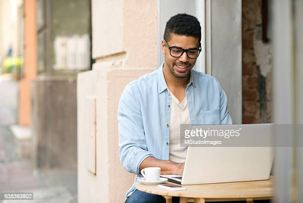 Handsome smiling man using laptop in caffee