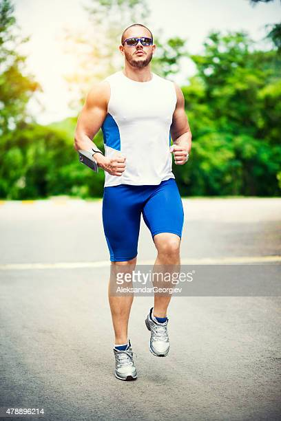 Handsome Strong Muscular Athletic Man Running Outdoors in Nature