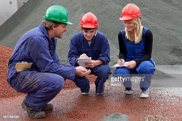 Beau étudiant faisant des notes. Apprentissage d'ouvrier du bâtiment.
