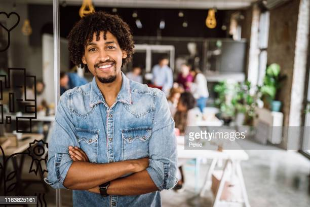 handsome successful african businessman representing his team - creative director stock pictures, royalty-free photos & images