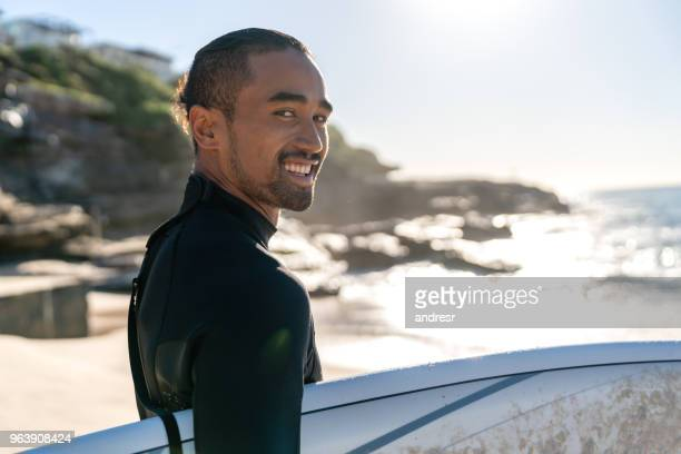 Handsome surfer carrying his board and looking at the camera smiling