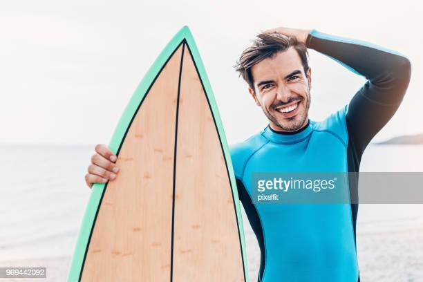 handsome surfer on the beach - one man only stock pictures, royalty-free photos & images