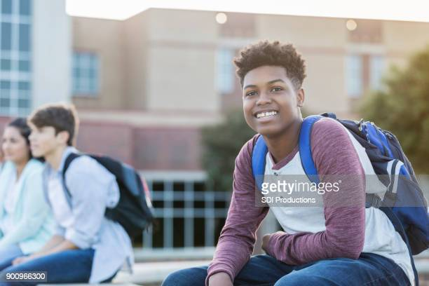 handsome teenage african american boy smiling while waiting outside high school - college application stock photos and pictures