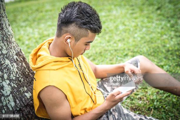 Handsome Thai man listening to his favorite playlist on smartphone outdoors