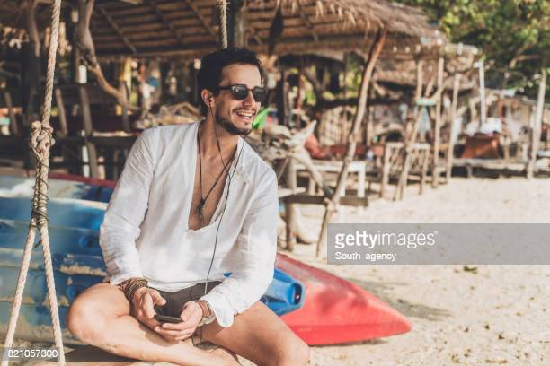 handsome tourist relaxing at the beach - handsome thai guy stock photos and pictures