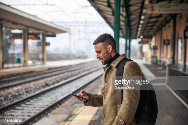handsome tourist watching content on his mobile phone waiting for train to come - stock photo - commuter stock pictures, royalty-free photos & images