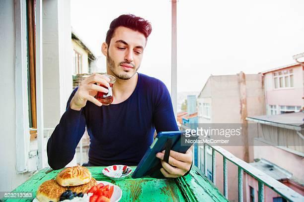 Gut aussehender Mann, die türkischen Medien zu seinem tablet während des Frühstücks