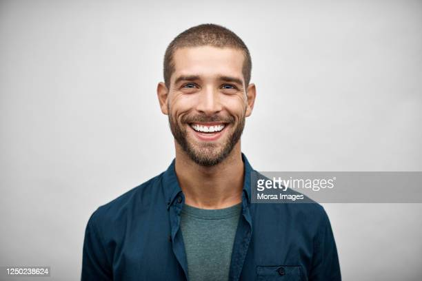 handsome young adult businessman with stubble - glimlachen stockfoto's en -beelden