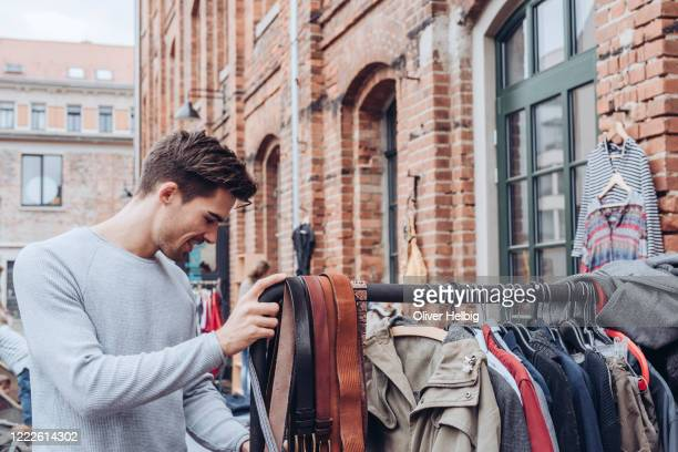 a handsome young adult man looking for second hand clothes at a flea market - flea market stock pictures, royalty-free photos & images