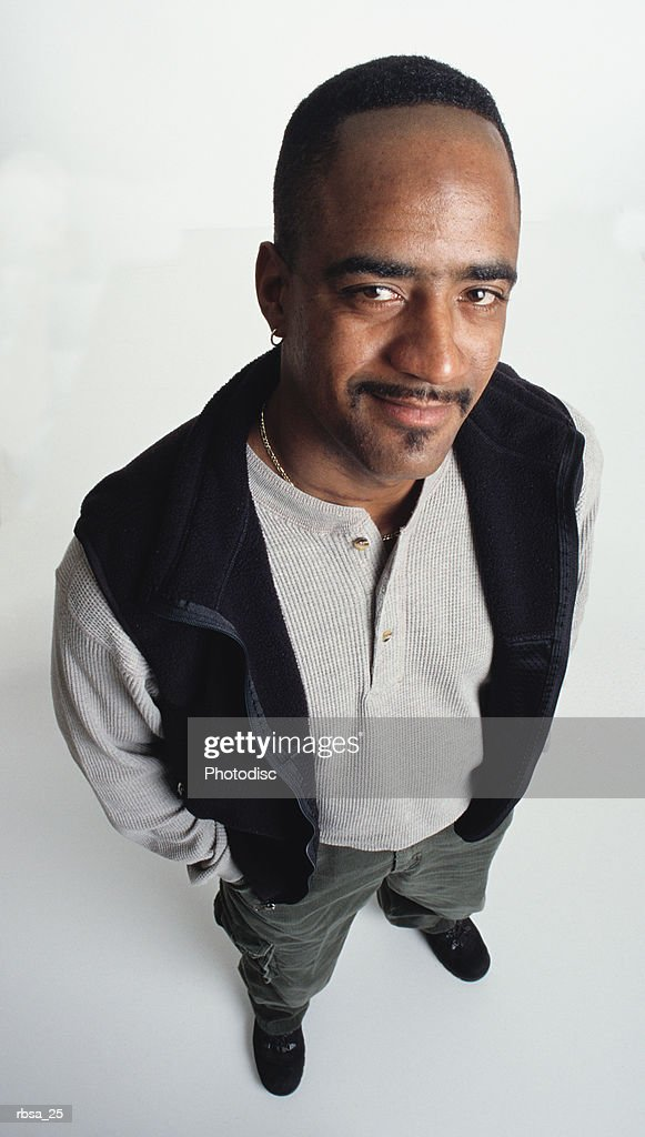handsome young african american adult male with short hair and an earring and facial hair wearing a fleece vest and khakis stands looking up at the camera with an apprehensive expression : Foto de stock