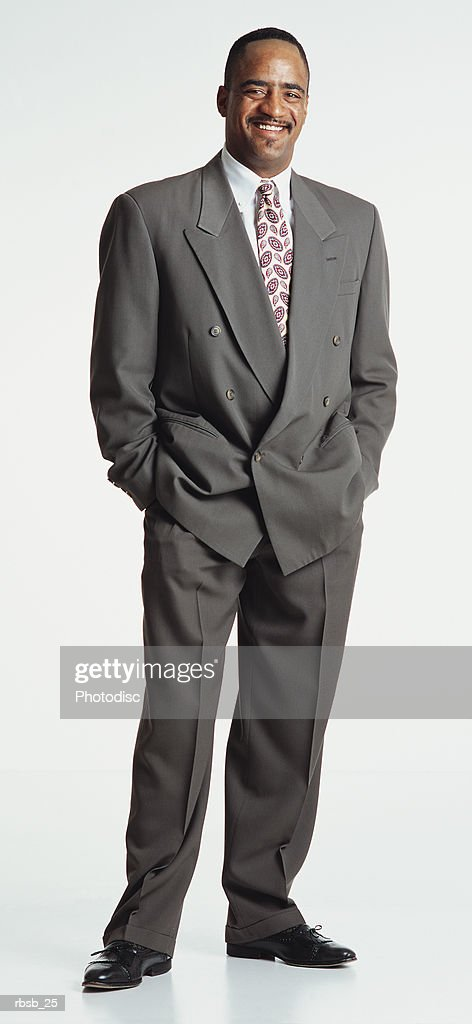 handsome young african american male in grey suit stands with his hands in pockets smiles to camera : Foto de stock