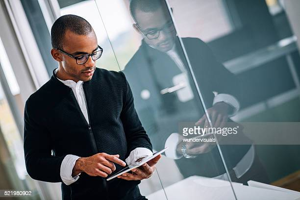 Handsome young African-american Entrepreneur working on tablet in business office