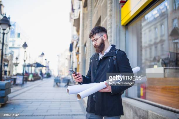 Handsome young architect commuting to work, using smart phone