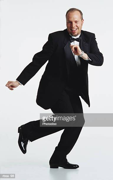 handsome young balding caucasian adult male goatee tuxedo bow tie running dance pose smiles happily