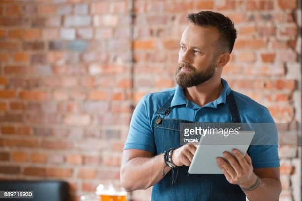 hübscher junge barkeeper mit digital-tablette - izusek stock-fotos und bilder
