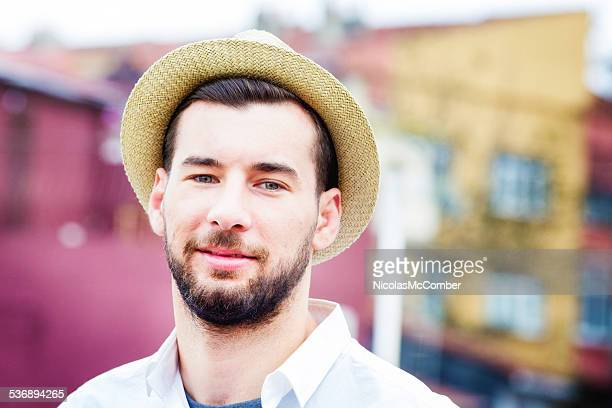 Handsome young bearded man rooftop portrait with straw hat