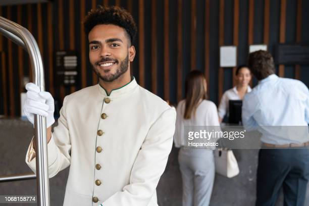 Handsome young black bellhop looking at camera smiling while holding luggage cart