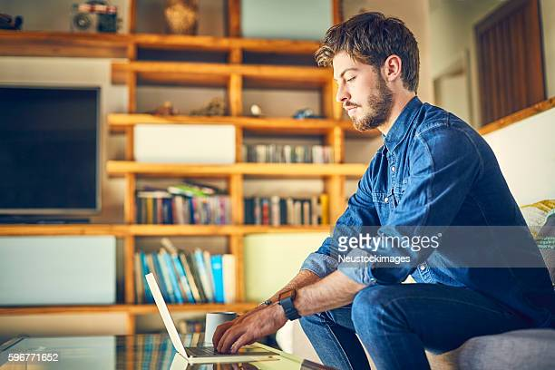 Handsome young blogger using laptop at coffee table at home