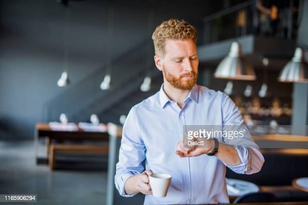 bel giovane uomo d'affari che controlla il tempo durante una pausa caffè. - caffè bevanda foto e immagini stock