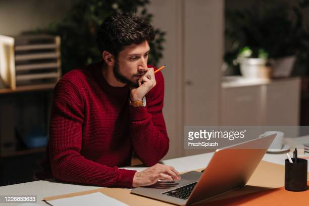 handsome young businessman in a red sweater working alone at the office late at night by using a laptop computer - red shirt stock pictures, royalty-free photos & images