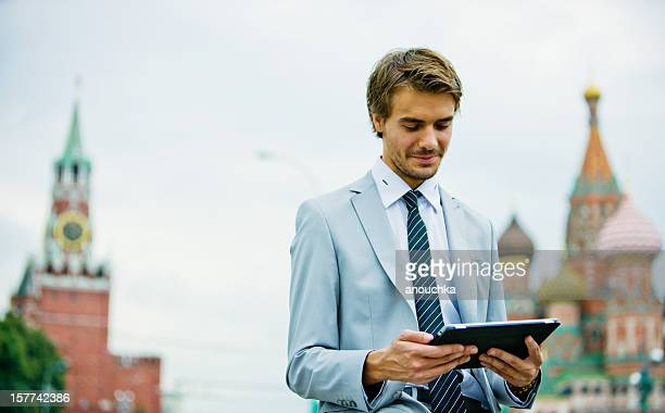 Handsome Young Businessman in Moscow holding Digital Tablet