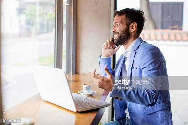 Handsome young businessman talking on his phone