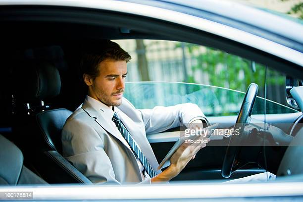 Handsome Young Businessman Using Digital Tablet in Car
