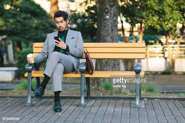 スマート フォンを使用してハンサムな青年実業家 - ベンチ ストックフォトと画像