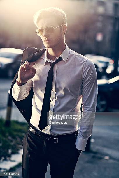 handsome young businessman walking in the street from work
