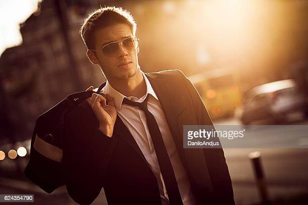 handsome young businessman walking in the street