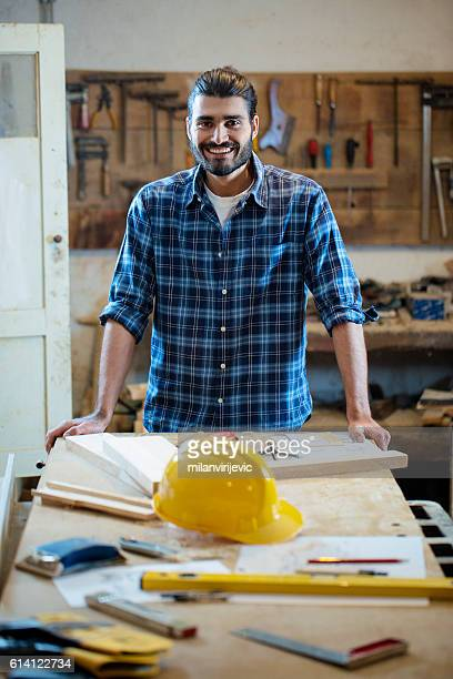 Handsome young carpenter in a workshop