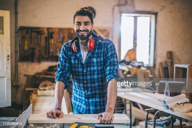 handsome young carpenter posing in his workshop - ear protection stock pictures, royalty-free photos & images