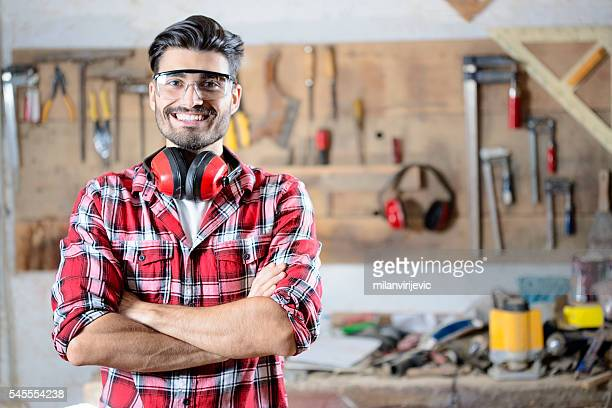 Handsome young carpenter posing in his workshop