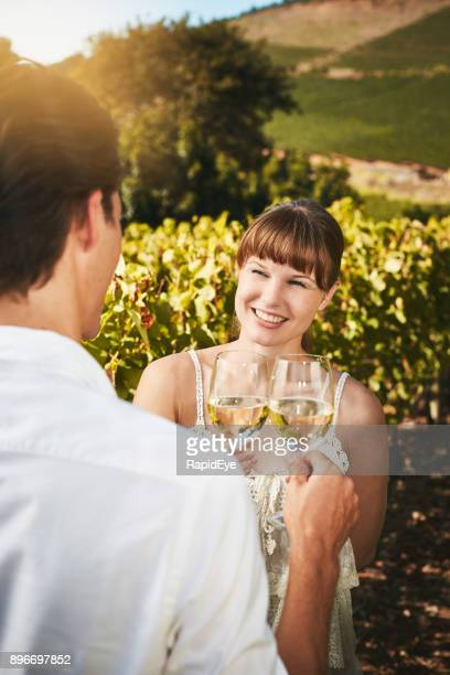 Handsome young couple in vineyard toast with white wine