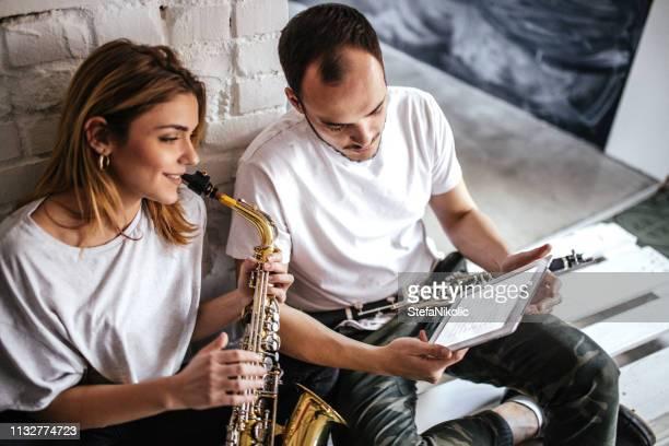 guapo joven pareja tocando saxofón - clarinete fotografías e imágenes de stock