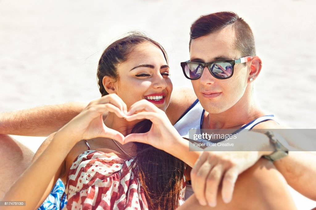 Handsome young couple sitting in the sand at the beach on a sunny day with heart sign : Stock Photo