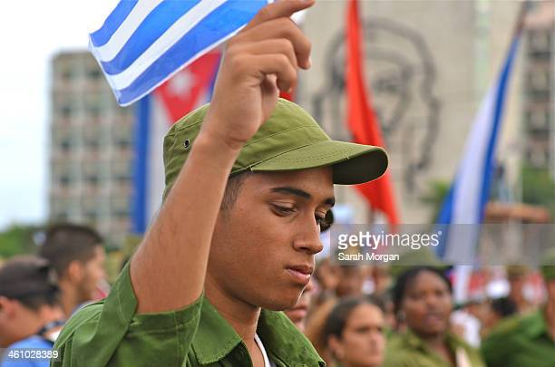 CONTENT] Handsome young Cuban soldier in front of Che Guevara mural Plaza de la Revolución Havana Cuba He is taking part in the May Day International...