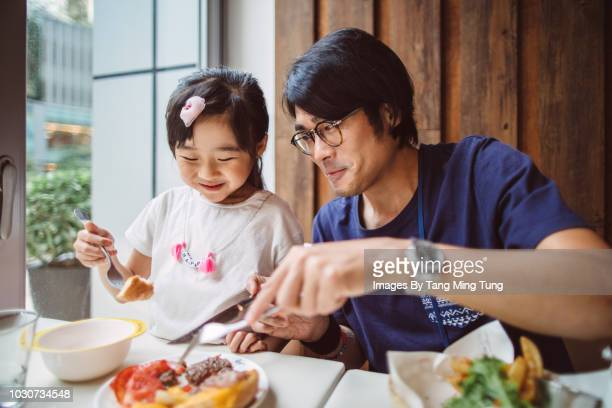 Handsome young dad having meal with his lovely little daughter in a restaurant joyfully.