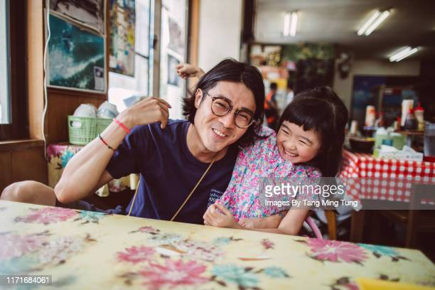 handsome young dad having meal with his lovely little daughter in a restaurant joyfully - 食卓 ストックフォトと画像