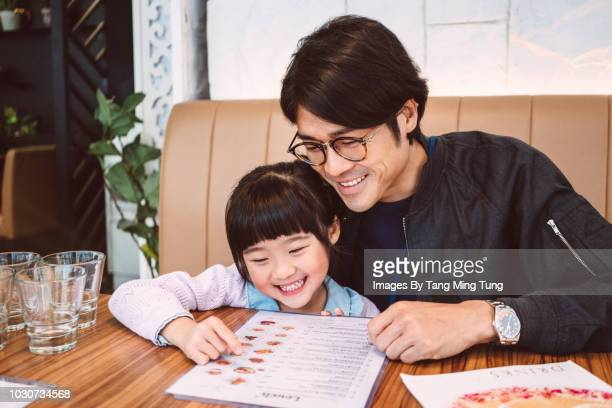 Handsome young dad looking at meal menu with his lovely little daughter in a restaurant joyfully.