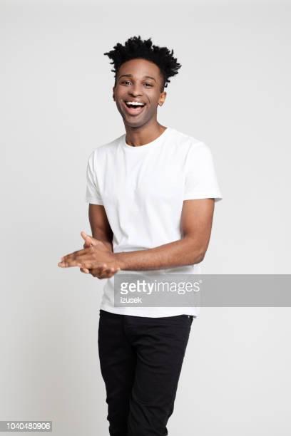 joven guapo en causales riendo sobre fondo blanco - pantalones negros fotografías e imágenes de stock