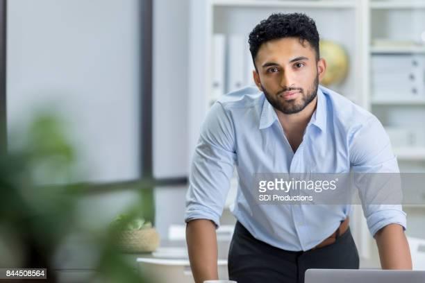 Knappe jonge Indiase zakenman aan het werk