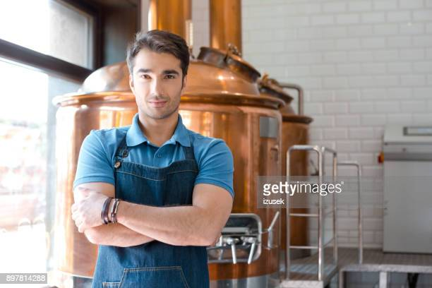 bel giovane barista maschio in piedi nel microbirrificio - izusek foto e immagini stock