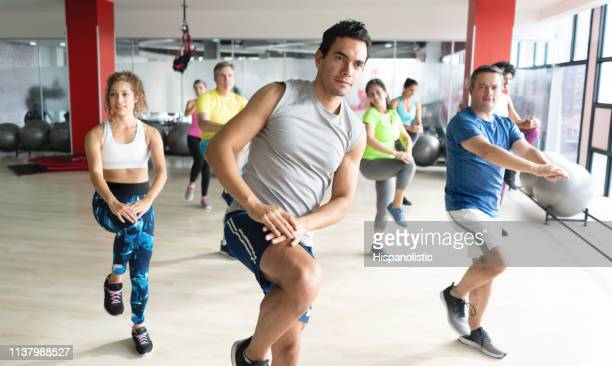 handsome young male instructor leading a boxing class at the gym and people following him - hispanolistic stock photos and pictures
