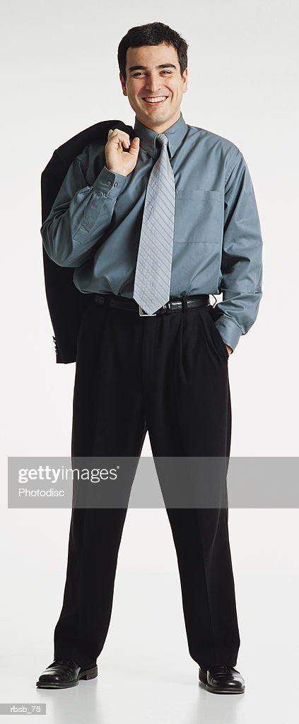 handsome young male short dark hair wears blue shirt slacks smiles to camera jacket over shoulder : Foto de stock