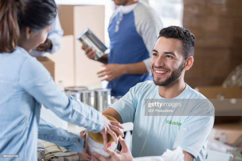 Handsome young male volunteer receives donations during food drive : Stock Photo
