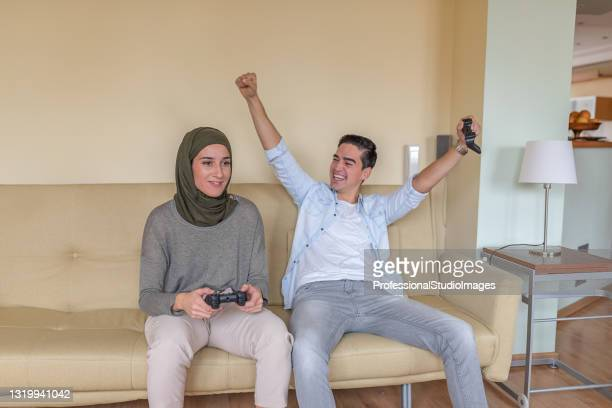 handsome young man and his middle eastern girlfriend are having fun with video games. - television host stock pictures, royalty-free photos & images