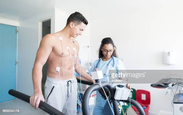 Handsome young man at the clinic doing a treadmill stress test and nurse taking his vital signs